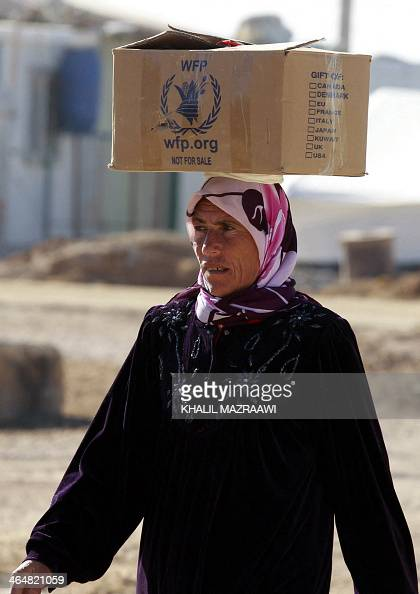A Syrian refugee carries on her head a box distributed by the World Food Program in an alley of the Zaatari refugee camp located close to the...