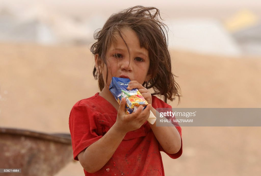 A Syrian refugee child drinks as families wait to enter Jordanian side of the Hadalat border crossing, a military zone east of the capital Amman, after arriving from Syria on May 4, 2016. According to the Jordanian Commander of the Border Guards Brigadier Saber Al-Mahayreh, around 5000 Syrians fleeing from recent attacks on the northern Syrian city of Aleppo are trying to cross into Jordan in search of safety and most are exhausted and desperately in need of help and medical treatment. MAZRAAWI