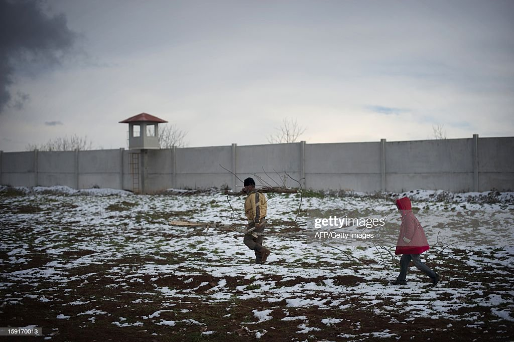 A Syrian refugee child helps a man to collect wood at a refugee camp in Bab al-Salama on the Syria-Turkey border, on January 9, 2013. The internally displaced Syrians faced further misery due to increasing shortage of supplies as heavy rain was followed by a drop in temperatures.
