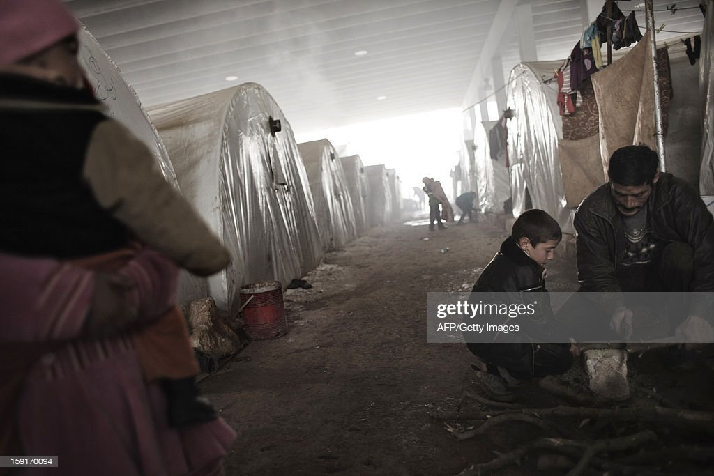 A Syrian refugee child helps a man to cut wood at a refugee camp near the northern city of Azaz on the Syria-Turkey border, on January 9, 2013. The internally displaced Syrians faced further misery due to increasing shortage of supplies as heavy rain was followed by a drop in temperatures.