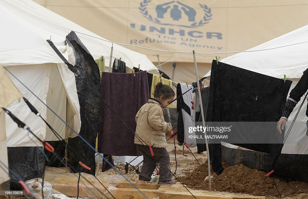 A Syrian refugee child makes her way through muddy ground at the Zaatari refugee camp, near the Syrian border with Jordan in Mafraq, on January 9, 2013. Thousands of Syrian refugees are appealing for help after three days of rain and winter storm left them battling mud, water, freezing temperatures and increasing misery. AFP PHOTO/KHALIL MAZRAAWI
