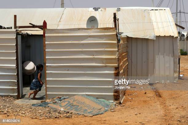 Syrian refugee child runs into her makeshift home at the Azraq camp for Syrian refugees the newest camp in Jordan that hosts 54000 refugees in...