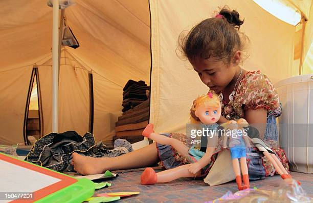 A Syrian refugee child who fled the violence in her country with her family plays with dolls at the Zaatari refugee camp close to the northern...