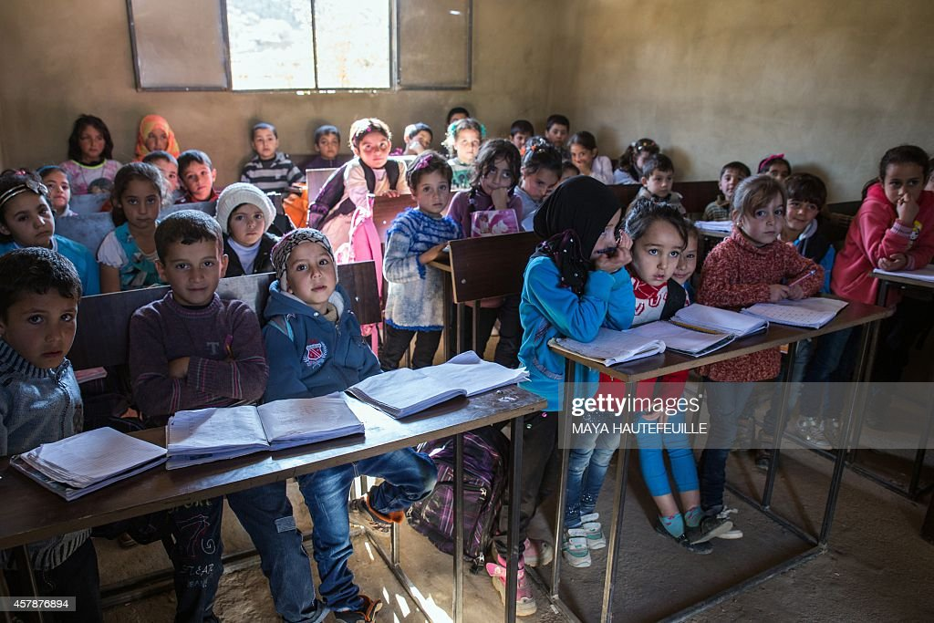 Syrian refugee children attend the Bunia Mustaqbal school in Lebanon's eastern town of Arsal on the border with Syria for the first time on October...