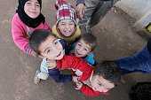 Syrian refugee children fled their homes due to the civil war in their country smile to the camera at Babel refugee camp in eastern Lebanese city of...