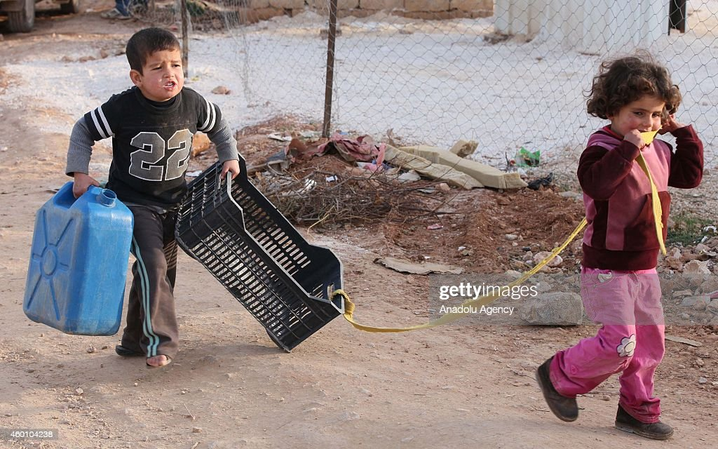 Syrian refugee children fled their homes due to the civil war in their country play with plastic materials at Babel refugee camp in eastern Lebanese...