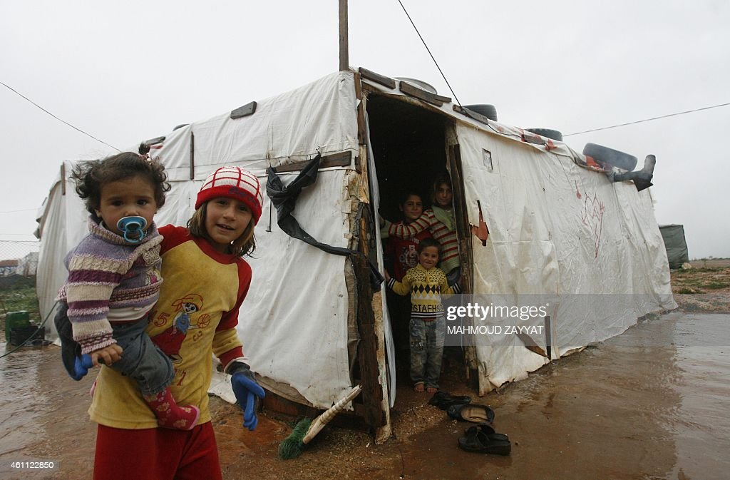 Syrian refugee children from the northwestern Syrian province of Idlib stand near their temporary shelter at a refugee camp in the southern Lebanese...