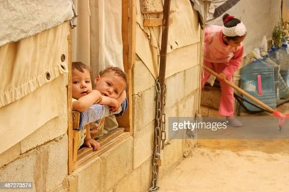 Syrian refugee children look on from a window during a sandstorm at a refugee camp on September 8 2015 near the Bekaa Valley village of Taalabaya Two...