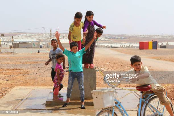 Syrian refugee children play and get wetted at a drinking water pumbing system under the hot sun near his makeshift home at the Azraq camp for Syrian...