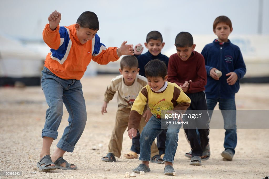ZA'ATARI, JORDAN - JANUARY 30: Syrian refugee children play in the Za'atari refugee camp on January 30, 2013 in Za'atari, Jordan. Record numbers of refugees are fleeing the violence and bombings in Syria to cross the borders to safety in northern Jordan and overwhelming the Za'atari camp. The Jordanian government are appealing for help with the influx of refugees as they struggle to cope with the sheer numbers arriving in the country.