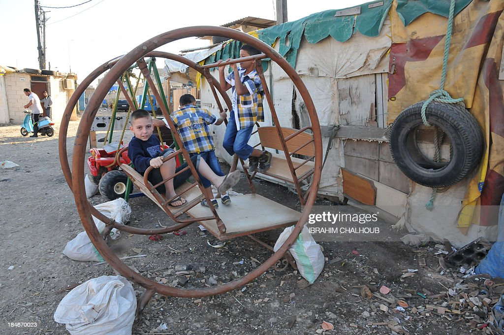 Syrian refugee children play on a swing in a poor seaside neighbourhood in the northern Lebanese city of Tripoli as Muslims around the world marked on October 15, 2013 the Eid al-Adha holiday or 'The Feast of Sacrifice' which commemorates Abraham's willingness to sacrifice his son Ismail on God's command.