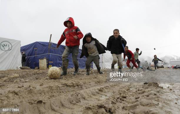 TOPSHOT Syrian refugee children play soccer under the rain at an unofficial refugee camp in the village of Deir Zannoun in Lebanon's Bekaa valley on...