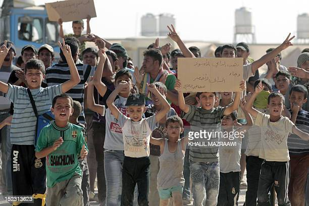 Syrian refugee children protest as UN Syria peace envoy Lakhdar Brahimi arrives at the at Zaatri refugee camp close to the northern Jordanian city of...