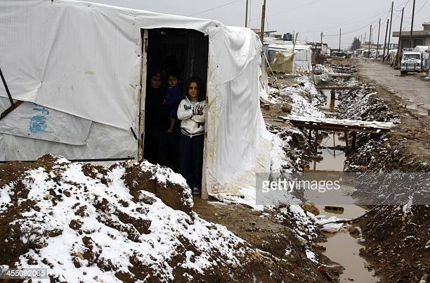 Syrian refugee children stand at the entrance of their makeshift house during a storm in the Dalhamiyyeh camp for Syrian refugees in the Lebanese...