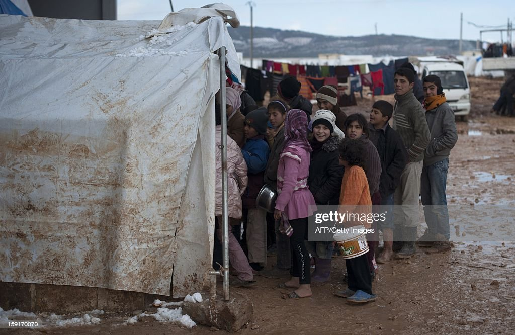 Syrian refugee children wait in freezing conditions for their families daily rations of food at a refugee camp in Bab al-Salama on the Syria-Turkey border, on January 9, 2013. The internally displaced Syrians faced further misery due to increasing shortage of supplies as heavy rain was followed by a drop in temperatures.