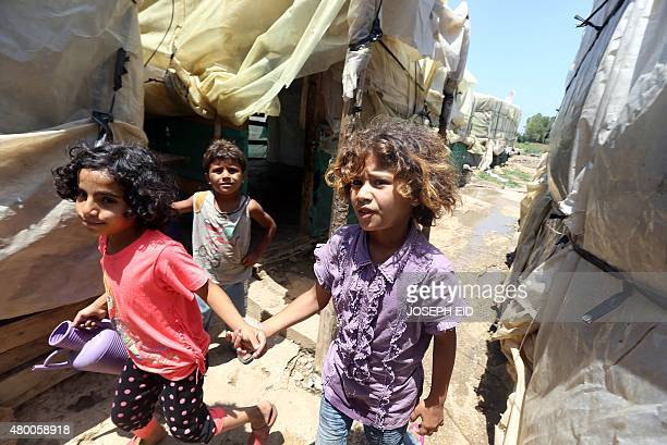 Syrian refugee children walk at an informal refugee camp in the area of Zahrani south of the Lebanese capital Beirut on July 9 2015 More than four...