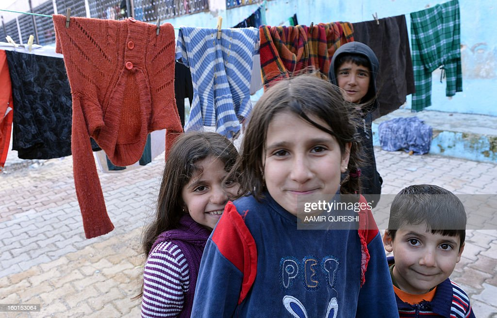 Syrian refugee children, who evacuated their homes due to shelling by regime forces, smile for a photo at a makeshift refugee camp setup in a school in Khirbet Al-Joz, in the northwestern Syrian province of Idlib, on January 22, 2013. In the green, mountainous part of northwest Syria, the boom of shells vibrate every few hours through dozens of villages abandoned by their terrified Kurdish inhabitants.