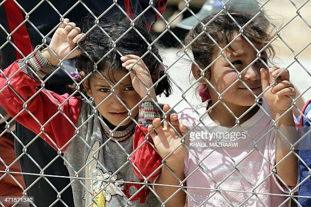 TAHA Syrian refugee children who fled the deadly conflict in their country look through a fence on April 28 2015 at Azraq refugee camp in Jordan some...