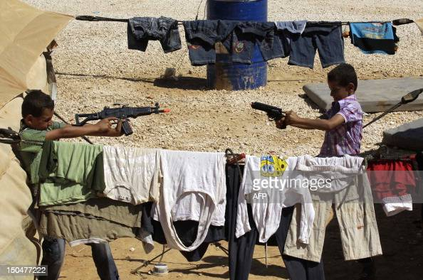 Syrian refugee children who fled the violence in their country play with guns at the Zaatari refugee camp close to the northern Jordanian city of...