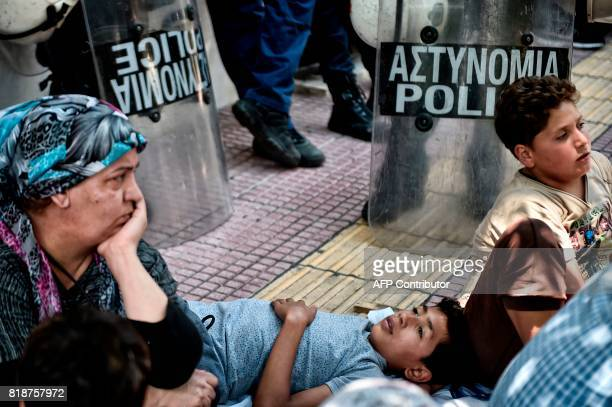 TOPSHOT Syrian refugee families sit or lie outside the German embassy in Athens on July 19 2017 during their protest against delays in the...
