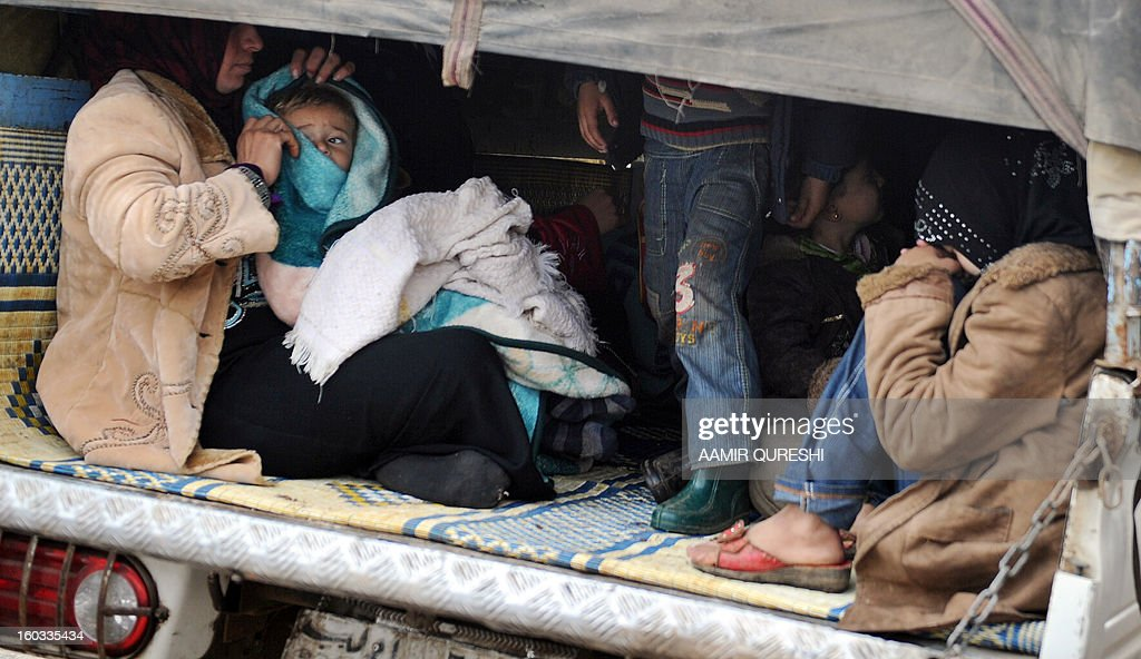 Syrian refugee families, who have evacuated their homes due to shelling and bombardment by pro-regime forces, sit in the back of a mini truck as they leave for neighbouring Turkey, in the village of Kfar Owaid in Idlib province, on January 29, 2013. In the back of small trucks so crammed that children have to loll on adults' legs, refugees are fleeing war-broken Syria for what they fear will be a long period in camps in neighbouring countries.