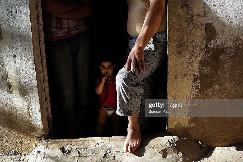 A Syrian refugee family from the city of Dara'a pauses in the home they share with extended members of their family in a poor neighborhood with a high concentration of Syrian refugees on July 01, 2013 in Beirut, Lebanon. Currently the Lebanese government officially hosts 546,000 Syrians with an estimated additional 500,000 who have not registered with the United Nations. Lebanon, a country of only 4 million people, is now home to the largest number of Syrian refugees who have fled the conflict. The situation is beginning to put a huge social and political strains on Lebanon as there is currently no end in sight to the war in Syria.