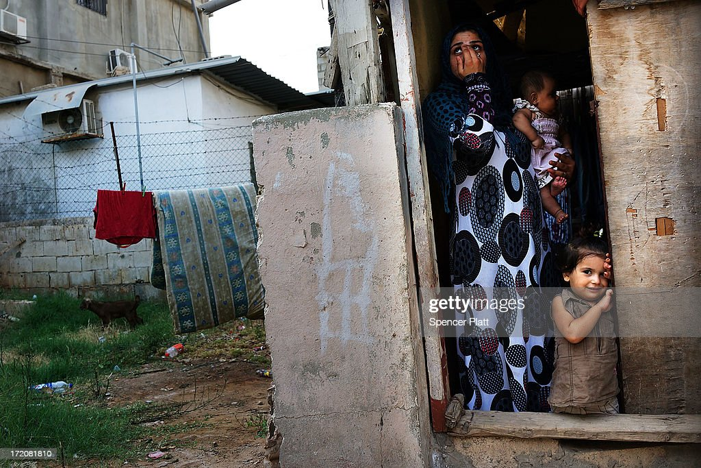 A Syrian refugee family from the Deir el Zour, Syria pauses in their doorway in a neighborhood with a high concentration of Syrian refugees on July 01, 2013 in Beirut, Lebanon. Currently the Lebanese government officially hosts 546,000 Syrians with an estimated additional 500,000 who have not registered with the United Nations. Lebanon, a country of only 4 million people, is now home to the largest number of Syrian refugees who have fled the conflict. The situation is beginning to put a huge social and political strains on Lebanon as there is currently no end in sight to the war in Syria.