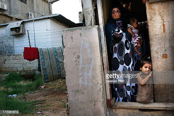 Syrian refugee family from the Deir el Zour Syria pauses in their doorway in a neighborhood with a high concentration of Syrian refugees on July 01...