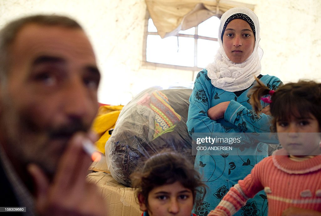 A Syrian refugee family gathers inside a tent after arriving to the Turkish side of the Orontes river after fleeing from the northern Syrian town of Darkush on December 13, 2012. The number of Syrian refugees registered in neighbouring countries and North Africa has passed half a million, the UN's refugee body said, adding that many more have not come forward to seek help. AFP PHOTO / ODD ANDERSEN