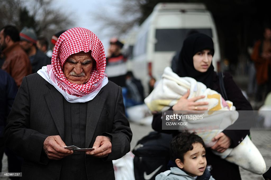 A Syrian refugee family waits after crossing the Syrian border on January 16 2014 in Karkamis near the town of Gaziantep south of Turkey Two weeks of...