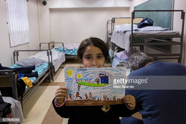 Syrian refugee Fatima Asaaid Alkhateb shows her drawing illustrating a child's dream in Syria in her family room in Joutseno reception center on...
