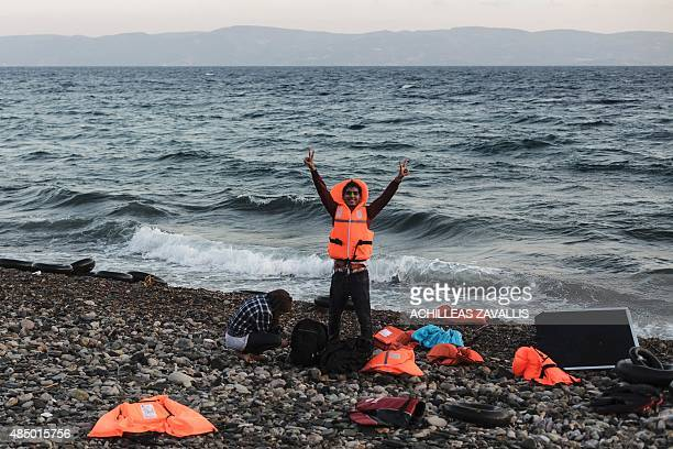A Syrian refugee flashes the victory sign after arriving on the shores of Lesbos island in Greece in an inflatable boat from Turkey on August 23 2015...