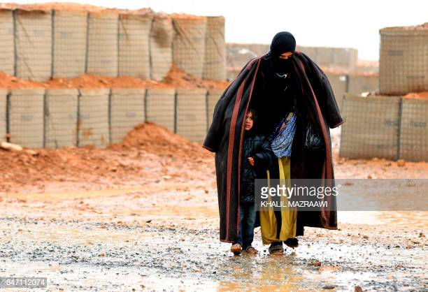 Syrian refugee from the informal Rukban camp which lies in noman'sland off the border between Syria and Jordan in the remote northeast walks in the...