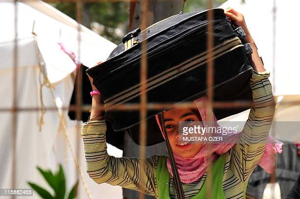 A Syrian refugee girl carries her bag after her arrival on June 10 2011 at the Turkish Red Crescent camp in the Yayladagi district of Turkish city of...