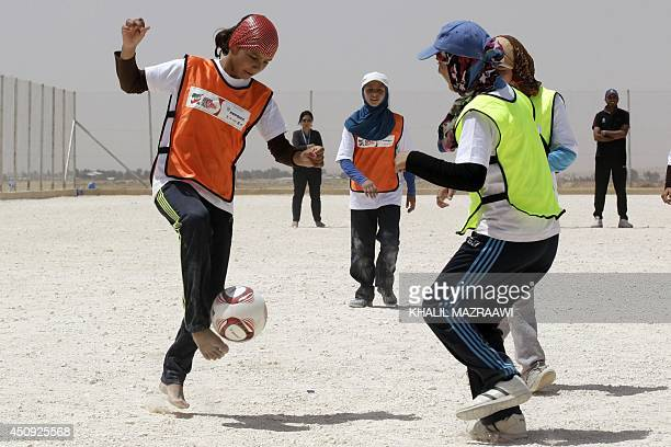 A Syrian refugee girl controls the ball during a match as part of the camp's football league at the Zaatari refugee camp located near the Jordanian...