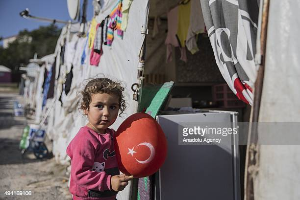 Syrian refugee girl fled from her home due to civil war poses with Turkish flag in Yayladagi YIBO camp in Hatay province of Turkey on October 25 2015