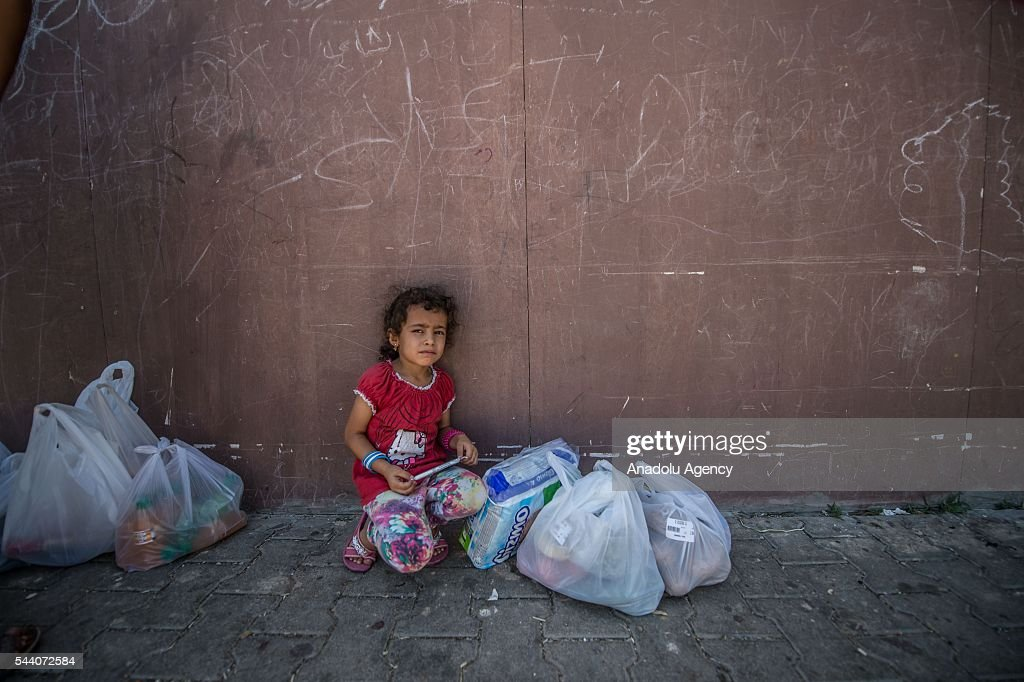 Syrian refugee girl is seen in front of refugee camp grocery in Suruc district of Sanliurfa, Turkey on July 01, 2016, as the Syrian people who fled the clashes between Daesh and Kurdish armed groups about two years ego, make preparations for the Eid al-Fitr marks the end of the Muslim holy fasting month of Ramadan by preparing sweets despite the all harsh conditions at the camp away from their home.