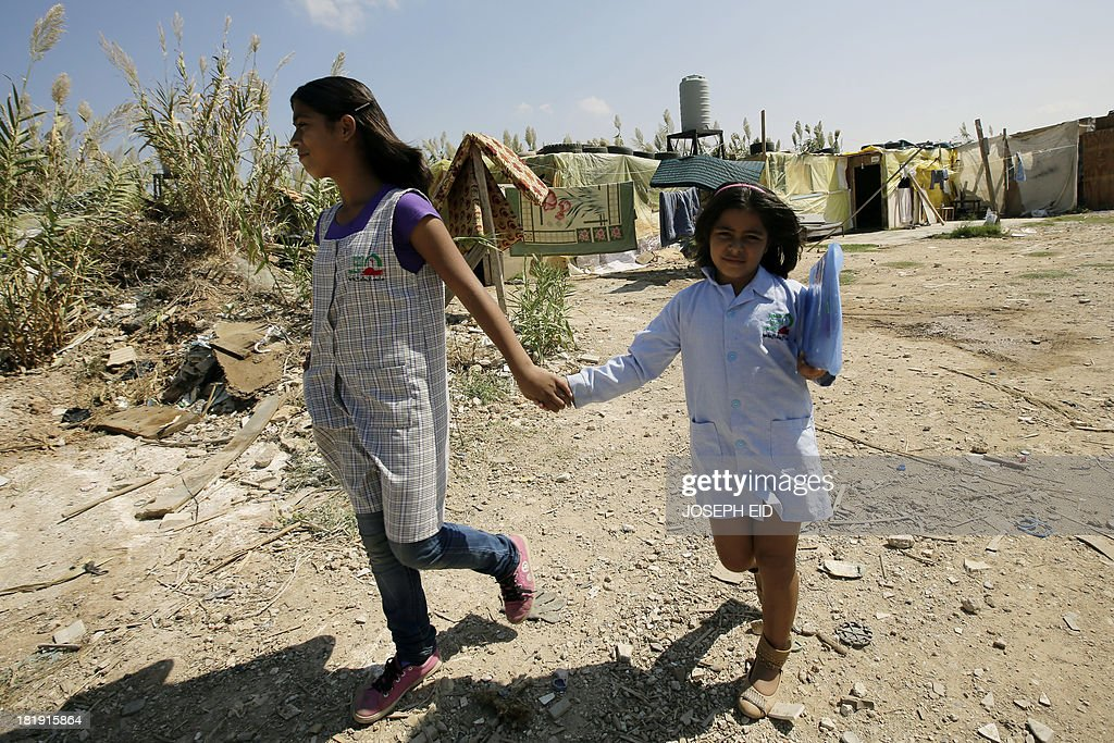 Syrian refugee girl Mashaael, 7, flanked by her sister Mariam, 13, carries documents as they leave their makeshift house heading to school on September 26, 2013 in the northern Lebanese city of Tripoli. UN children agency UNICEF said 257,000 Syrian children were seeking education in Lebanon in 2013, a number that could rise up to 400,000 next year. Mashaael was not able to register at school as she didn't meet the Lebanese public school system's standards. AFP PHOTO/JOSEPH EID