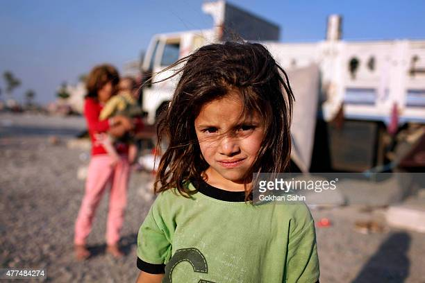 Syrian refugee girl pose as her family lives in their makeshift shelter near a truck close to the Turkish border post of Akcakale province of...