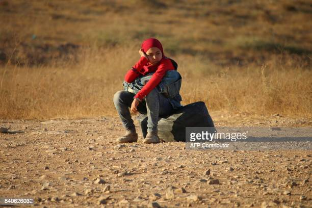 A Syrian refugee girl sits on the side of the road as she returns to Syria with her family after crossing the Jordanian border near the town of Nasib...