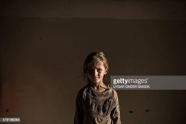 A Syrian refugee girl stands in a building on June 27 2015 in Syrian Kurdish city of Amuda after running away from clashes between regime forces and...