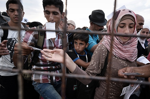 Syrian refugee hands over tickets prior to boarding a ferry bound for the Piraeus harbour at the port of Kos, on the Aegean island of Kos, on August 14, 2015