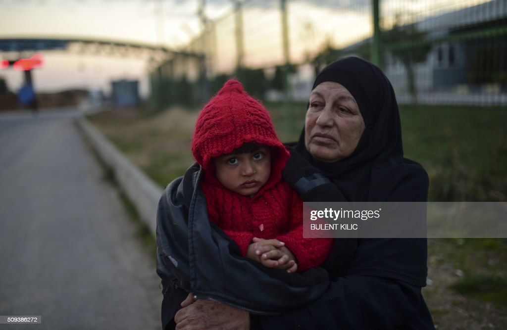 Syrian refugee Hatice Henidil hugs her grandson Usame while waiting for Usame's parents still stuck on the Syrian side of the border, in front of the Oncupinar crossing gate, near the town of Kilis, in south-central Turkey, on February 10, 2016. Syrian people wait to return to Syria, at the Turkish Oncupinar crossing gate, near the town of Kilis, in south-central Turkey. Around 30,000 Syrians are at the Turkish border after fleeing a Russia-backed regime offensive on the northern region of Aleppo, Turkish Prime Minister Ahmet Davutoglu said on February 8, as his country faces mounting pressure to open its border. Davutoglu said the refugees would be admitted if need be, although Turkey should not be expected 'to shoulder the refugee issue alone.'. / AFP / BULENT KILIC