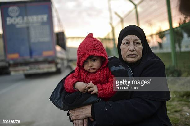 Syrian refugee Hatice Henidil hugs her grandson Usame while waiting for Usame's parents still stuck on the Syrian side of the border in front of the...