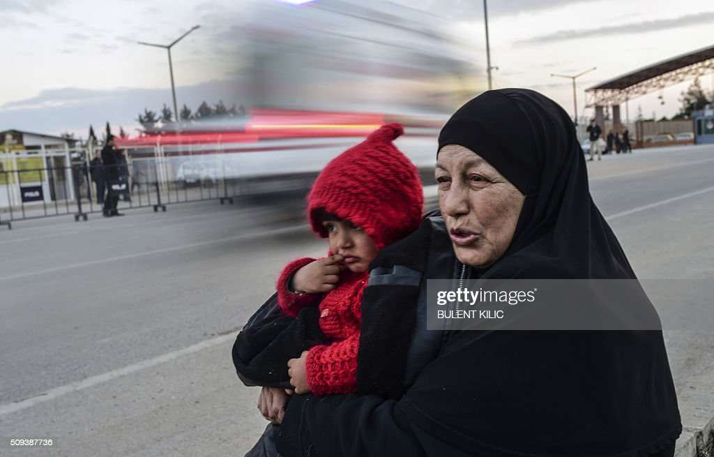 Syrian refugee Hatice Henidil hugs her grandson Usame while waiting for Usame's parents still stuck on the Syrian side of the border at the Oncupinar crossing gate, near the town of Kilis, in south-central Turkey, on February 10, 2016. Syrian people wait to return to Syria, at the Turkish Oncupinar crossing gate, near the town of Kilis, in south-central Turkey. Around 30,000 Syrians are at the Turkish border after fleeing a Russia-backed regime offensive on the northern region of Aleppo, Turkish Prime Minister Ahmet Davutoglu said on February 8, as his country faces mounting pressure to open its border. Davutoglu said the refugees would be admitted if need be, although Turkey should not be expected 'to shoulder the refugee issue alone.' / AFP / BULENT KILIC