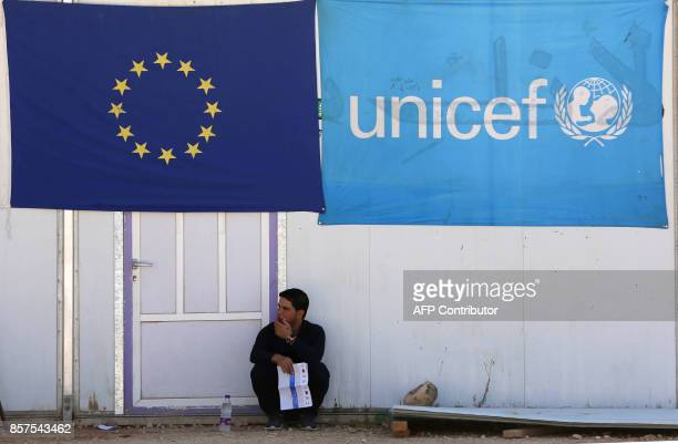 A Syrian refugee holds a pamphlet as he waits to register his name at the Zaatari office for employment on October 4 2017 at the Zaatari refugee camp...