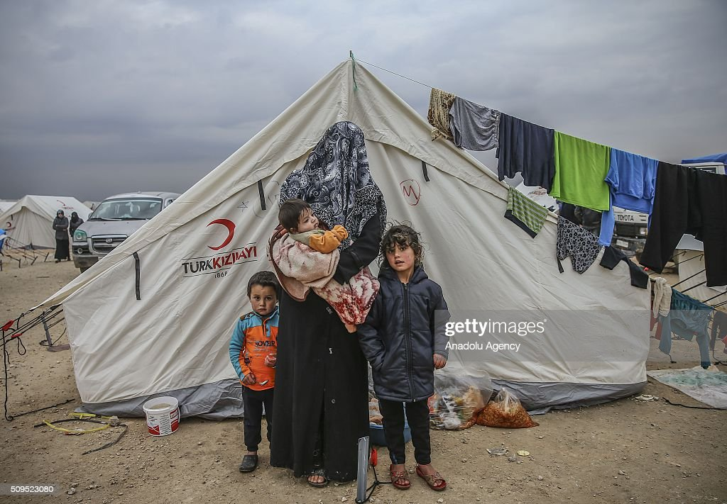Syrian refugee kids Alil, Isra (R) and Abdourrahman Ali (L), who fled bombing in Aleppo, is seen on their mother Emine Zaden at a tent city close to the Bab al-Salam border crossing on Turkish-Syrian border near Azaz town of Aleppo, Syria on February 11, 2016. Russian airstrikes have recently forced some 40,000 people to flee their homes in Syrias northern city of Aleppo.