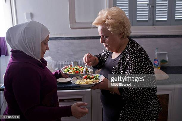 Syrian Refugee Lama Asaaid Alkhateb offers a traditional Syrian dish she has made to a Greek friend as they say goodbye two days before their family...
