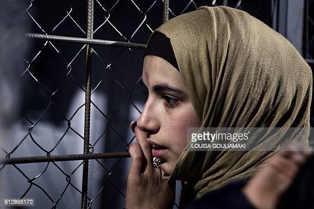 A Syrian refugee leans against the fence as she waits for the opening of the border to cross into Macedonia at the GreekMacedonian border near the...