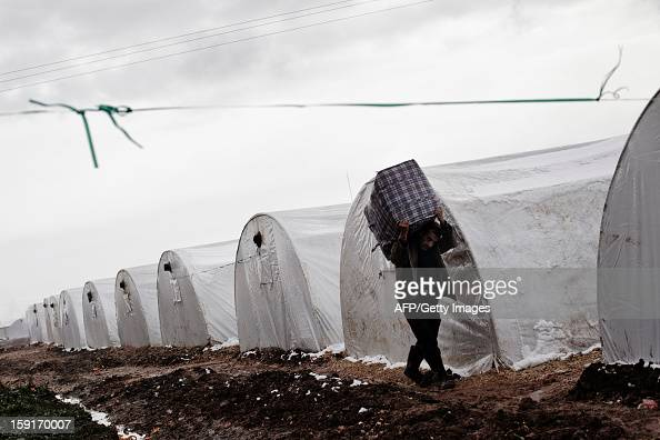 A Syrian refugee man carries a bag at a refugee camp near the northern city of Azaz on the SyriaTurkey border on January 9 2013 The internally...